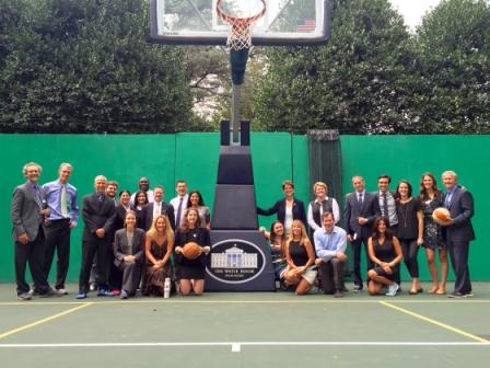 Athletes pose in front of a basketball hoop after participating in a meeting to discuss climate action and preparedness at the White House.