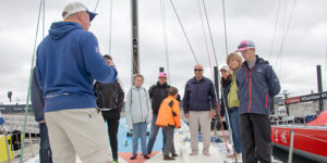 Pictured above: Mudratz sailors met with Anderson Reggio during the Volvo Ocean Race Newport Stopover and got a tour of Vestas 11th Hour Racing. Photo credit: Outrageous Photography